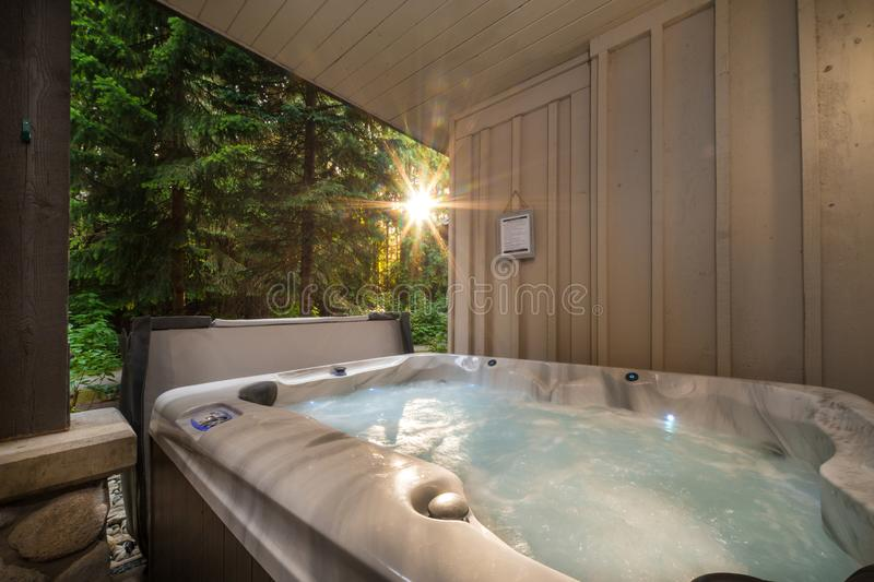 A outdoor hot tub near a forest with a sunburst coming through the trees. royalty free stock photos