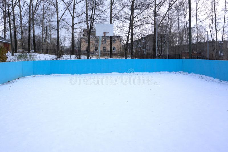 An outdoor ice skating rink and a hockey net with tall frost covered trees in the background in a winter landscape.  royalty free stock photo