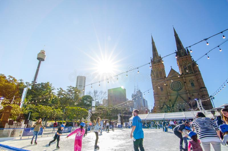 Outdoor ice skating rink at St Mary's Cathedral Square in winter season with sunshine day. SYDNEY, AUSTRALIA. – On July 9, 2017. - Outdoor ice stock image