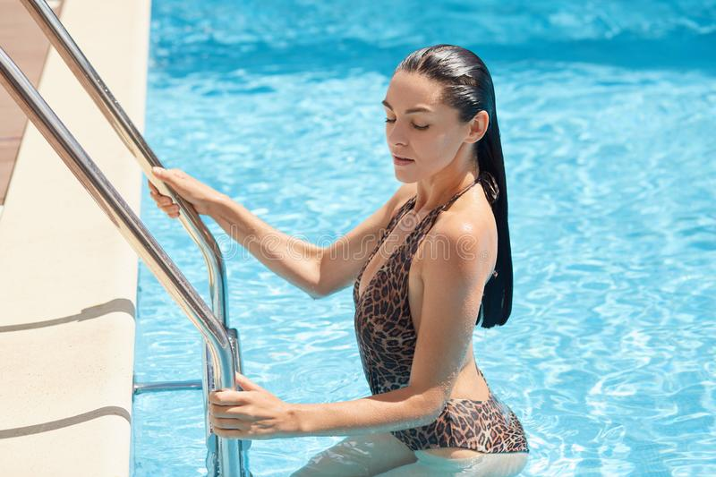 Outdoor image of delighted slender brunette staying in swimming pool, touching stairs, making pause in water exercises, coming out stock photography