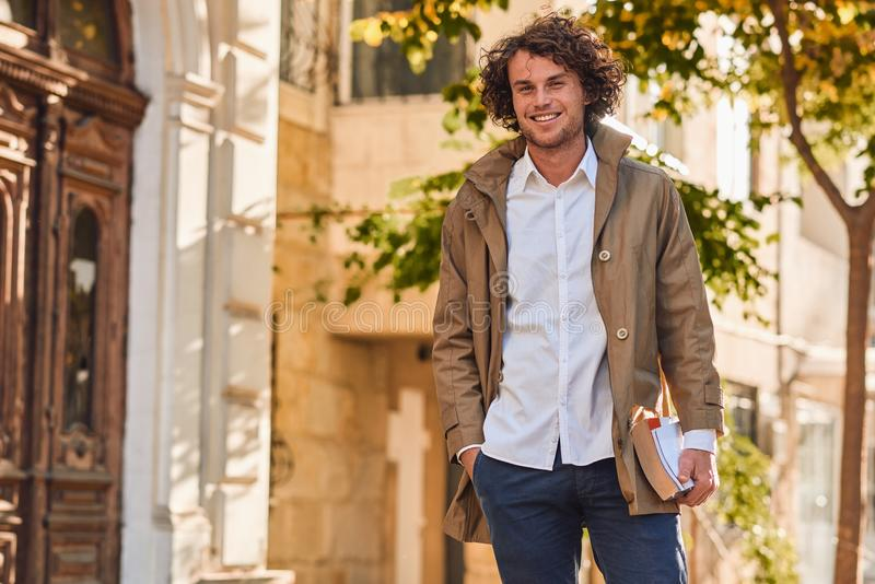 Outdoor image of handsome young man with books outdoors. College male student carrying books in college campus in autumn street. Background. Smiling cheerful royalty free stock photography