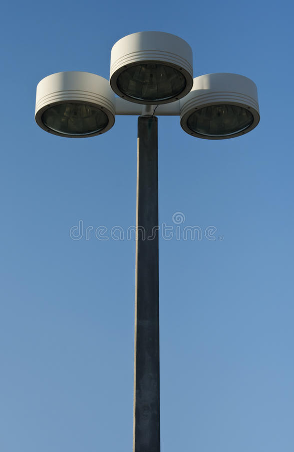 Outdoor lamp post. Centered outdoor lamp post or light pole with three lamp heads against bright blue sky with copy space stock photo