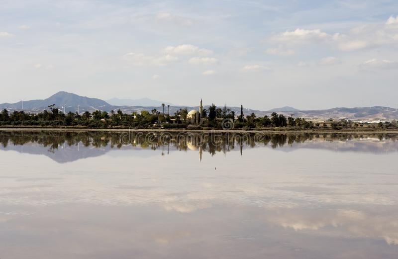 Outdoor landscape of Hala Sultan tekke in Cyprus with water reflections. And cloudy sky royalty free stock image