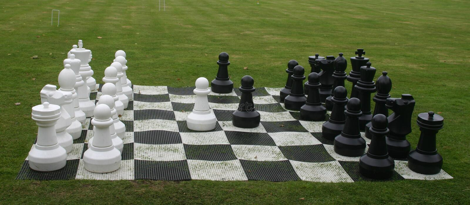 Outdoor chess game. Outdoor large size chess set laid out on a grass lawn. Pieces appear to be in the correct places stock image