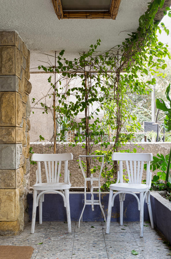Outdoor leisure corner with two wooden white chairs royalty free stock photography