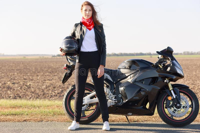 Outdoor lifestyle concept. Self confident female biker dressed in black clothes and red bandana on neck, holds helmet, poses on ro. Ad near her modern fast bike stock photo