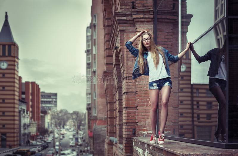 Outdoor lifestyle portrait of pretty young girl, going on the edge of high building parapet, wearing hipster swag dress, urban royalty free stock image