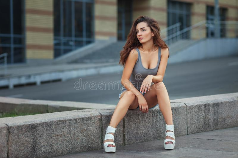 Outdoor lifestyle portrait of pretty young girl posing on stairway, wearing in hipster urban style on urban background royalty free stock images