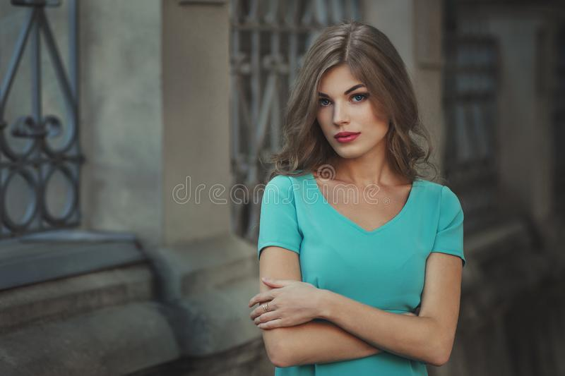 Outdoor lifestyle portrait of pretty young girl, wearing in blue dress on urban background. Creative color toned image royalty free stock image