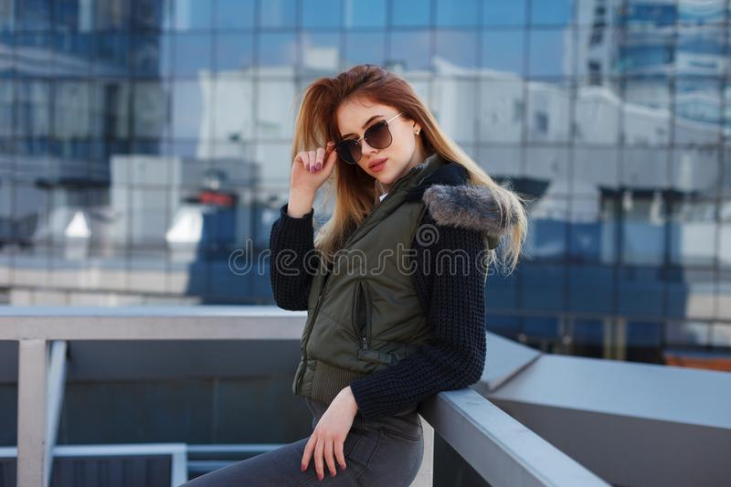 Outdoor lifestyle portrait of pretty young girl, wearing in hipster swag grunge style urban background royalty free stock image