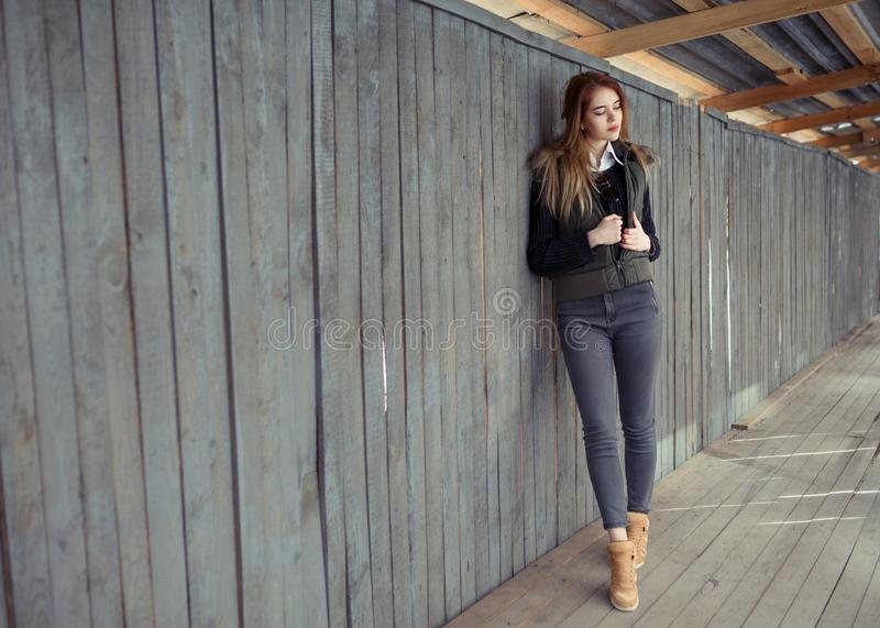 Outdoor lifestyle portrait of pretty young girl, wearing in hipster swag grunge style urban background. Retro vintage toned image. Film simulation stock photography