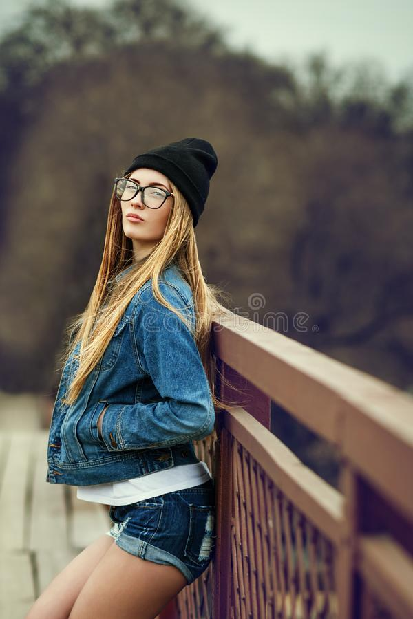 Outdoor lifestyle portrait of pretty young girl, wearing in hipster swag grunge style urban background. Retro vintage toned image. Film simulation stock images