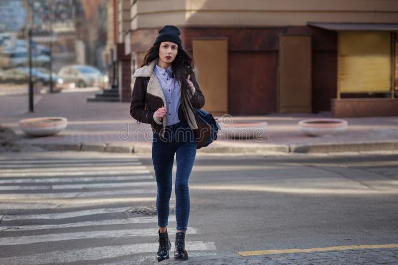 Outdoor lifestyle portrait of pretty young girl, wearing in hipster swag grunge style on urban background. Wearing hat and jeans royalty free stock images