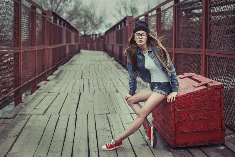 Outdoor lifestyle portrait of pretty young sitting girl, wearing in hipster swag grunge style urban background. Retro vintage royalty free stock photography