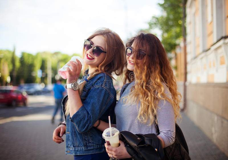 Outdoor lifestyle portrait of two happy best friend girls walk laugh talk and drink lemonade. Girls laugh at the joke royalty free stock images