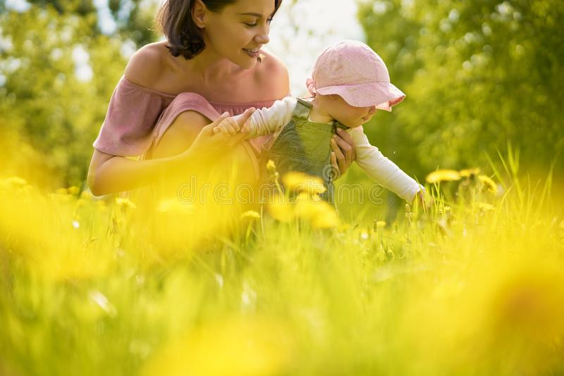 Mother and daughter on a meadow with dandelions royalty free stock image