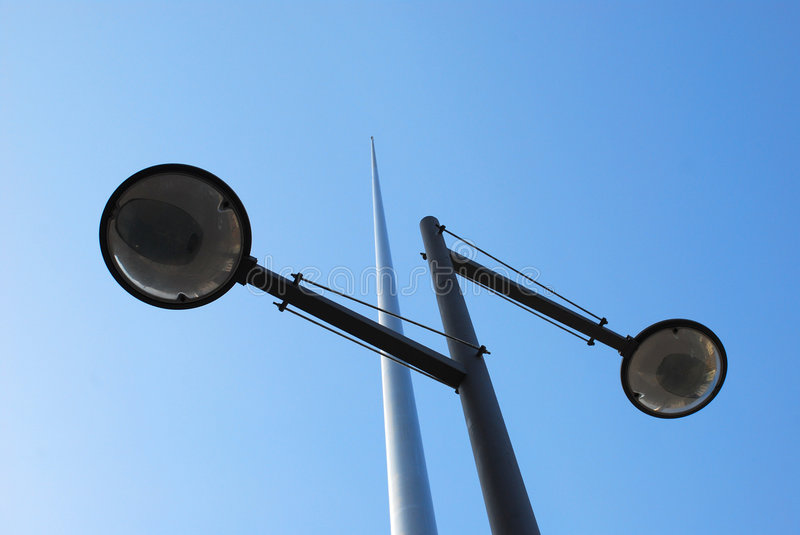 Outdoor lights. Underside view or two outdoor lights with tall metal pole and blue sky background royalty free stock image