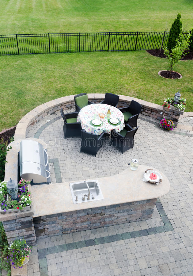 Outdoor living area on an open-air patio. View looking down at a brick paved outdoor living area on an open-air patio with a gas BBQ and concrete kitchen counter royalty free stock image