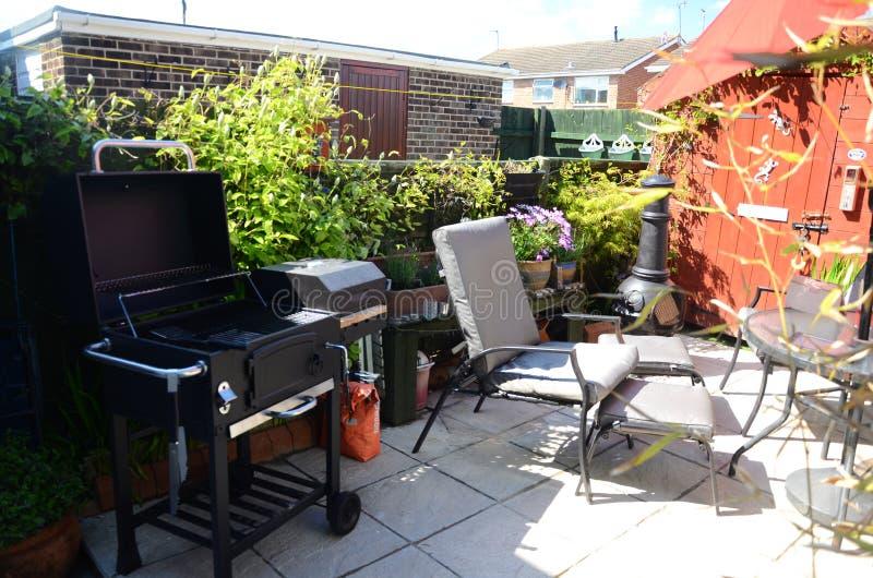 Outdoor living, barbecue time in the garden. Outdoor living, barbecue time in the home patio garden, small leisure area stock photos
