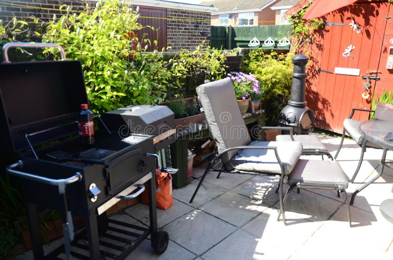 Outdoor living, barbecue time in the garden. Outdoor living, barbecue time in the home patio garden, small leisure area stock image