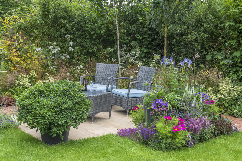 Outdoor living - in the garden. Outdoor living, chairs and table set up in the garden stock photos