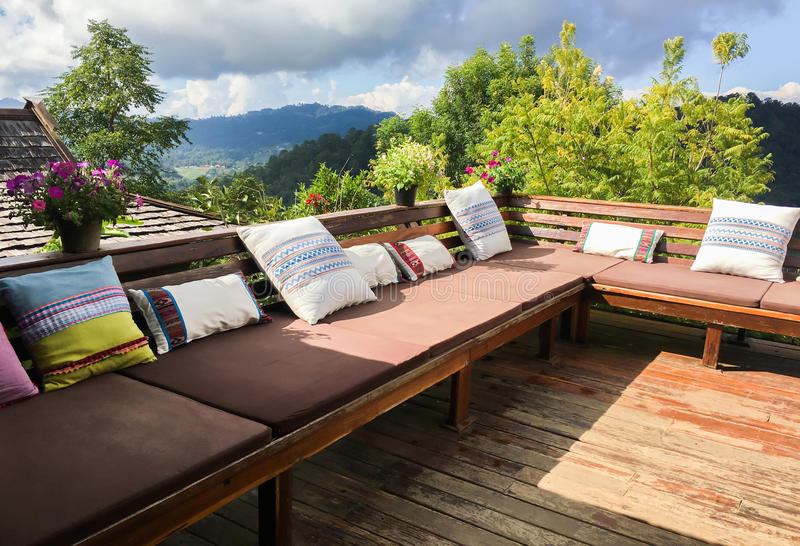 Outdoor living room or balcony with pillows. With mountain and forest background - home decoration royalty free stock images