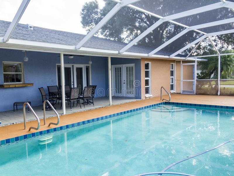 Outdoor living space attached to pool cage. Swimming pool with cage attached to house in outdoor living space used for entertaining royalty free stock photos