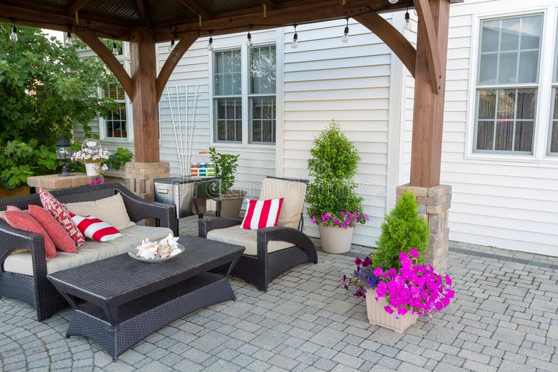 Outdoor living space on a brick patio. With covered gazebo and comfortable furniture with colorful striped cushions royalty free stock images