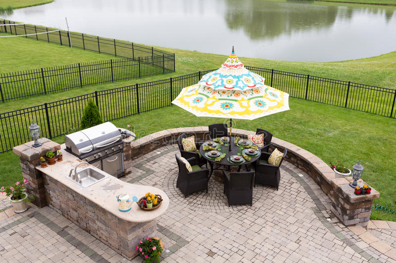 Outdoor living space ready for dinner. Outdoor living space on a brick patio overlooking a tranquil lake and fenced green lawn with a table under a sunshade or royalty free stock image