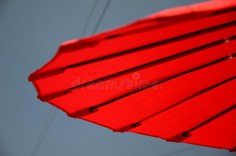 Outdoor living, sun parasol in the garden. Outdoor living, red chines sun parasol in the garden, shade from the sun royalty free stock images