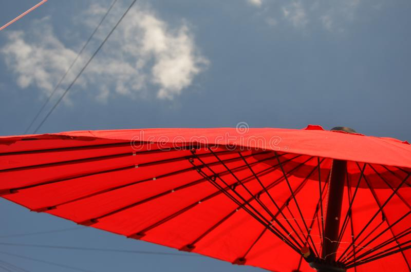 Outdoor living, sun parasol in the garden. Outdoor living, red chines sun parasol in the garden, shade from the sun royalty free stock photography