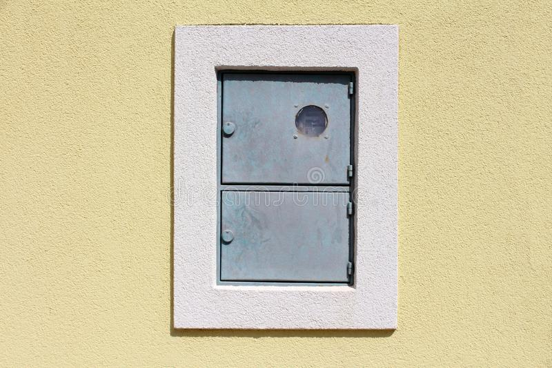 Outdoor locked metal electrical meter box with switch box mounted on house wall with new facade surrounded with white frame. On warm sunny day royalty free stock image