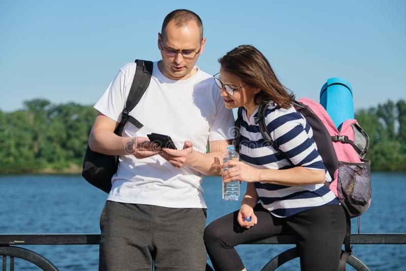 Outdoor mature couple using smartphone, man and woman talking walking in the park royalty free stock image