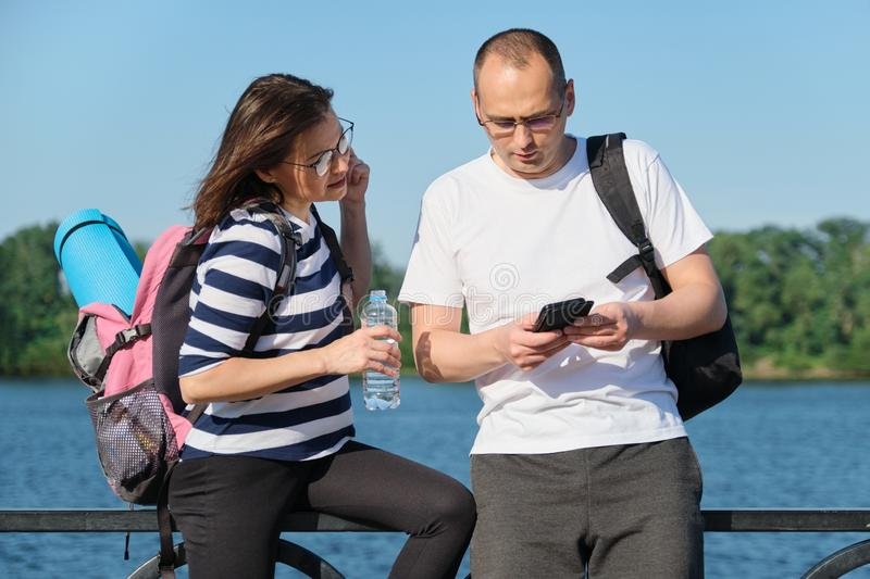 Outdoor mature couple using smartphone, man and woman talking walking in the park. People in sportswear with bottle of water, summer sunny evening near the stock photography