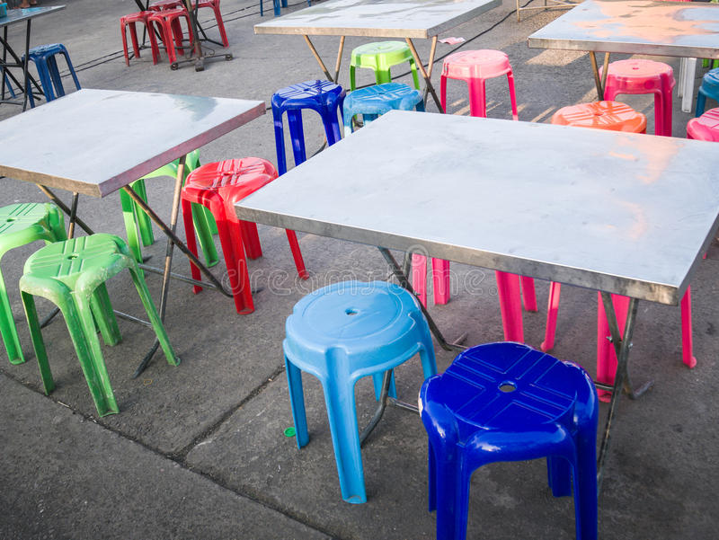 Outdoor metal table and colored plastic chair, street food scene in Thailand. Nobody stock photography