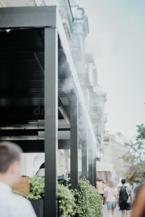 Outdoor Misting Systems, Mist Cooling Systems in summer street Cafe. Artificial fog system. Water mist machine creates coolness on stock image