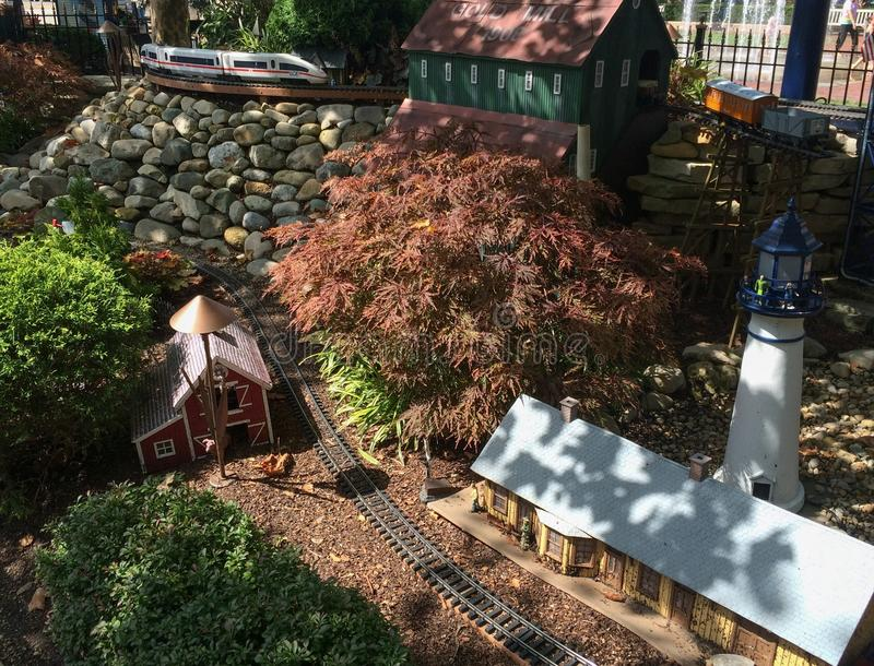 Outdoor model train track with train station lighthouse and barn. Cute outdoor train track set up, with model train station, lighthouse, barn, Japanese maple stock photos