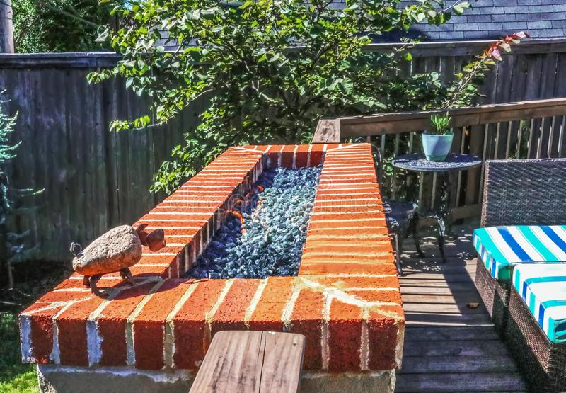 Outdoor natural gas fire pit with low flames on patio with privacy fence in background and colorful seating stock photography
