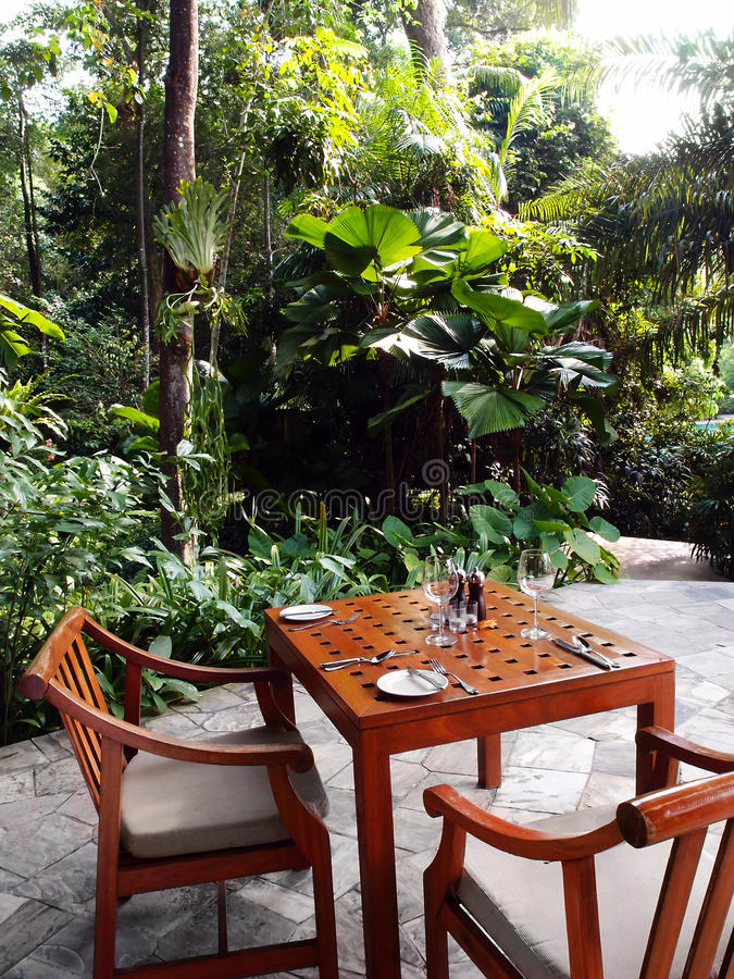 Outdoor patio dining area, tropical garden royalty free stock image