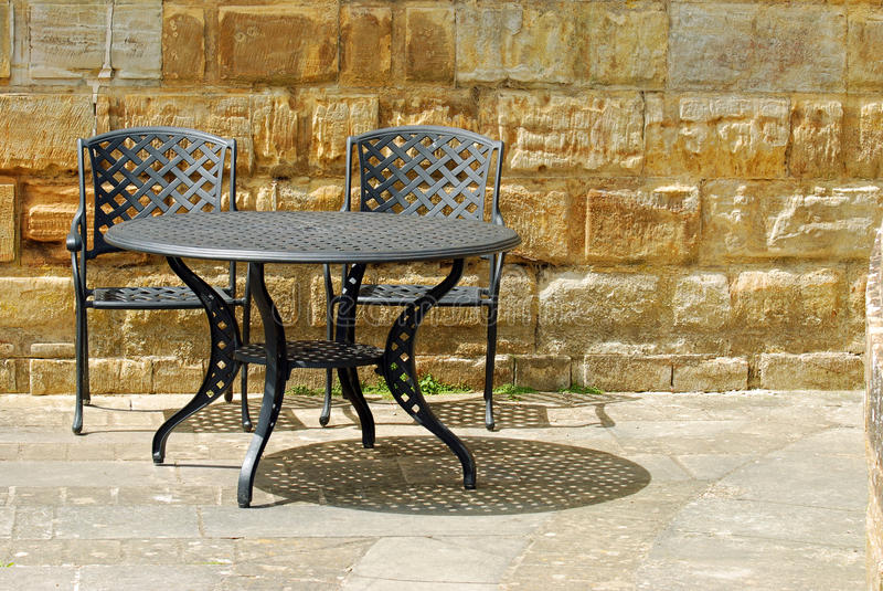 Outdoor patio set with rock wall royalty free stock images