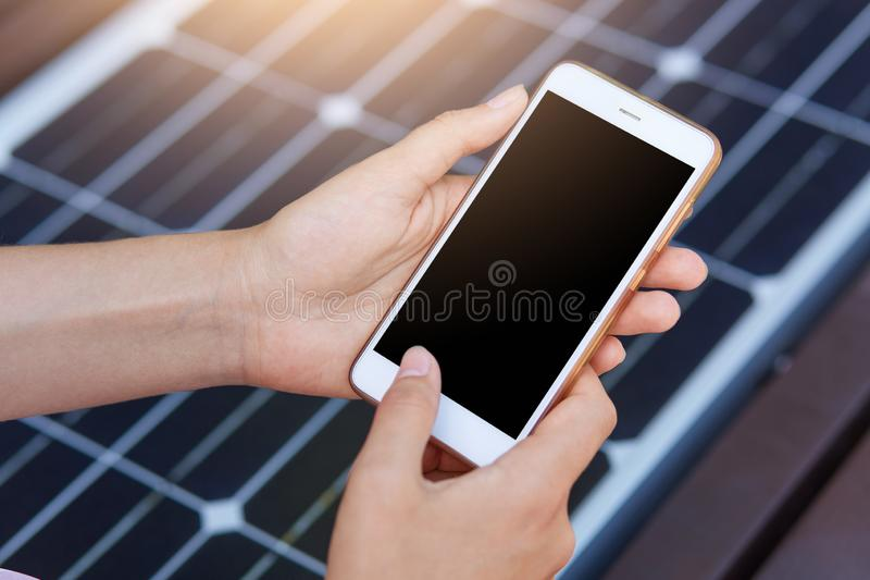 Outdoor photo of faceless person harging mobile phone via USB. Public charging on bench with solar panel on city street. royalty free stock photos