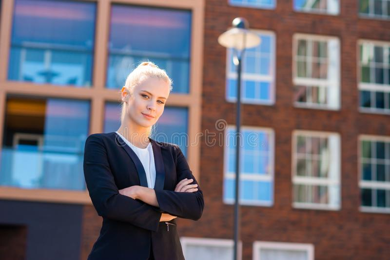 Outdoor photo of young and attractive businesswoman, retailer or student. Woman in casual wear. Real estate, business stock photo