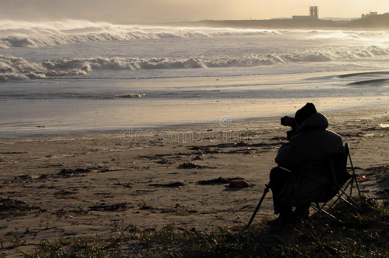 Outdoor photography. A photographer photographing the ocean waves during the dusk...image against the sunlight,without colors alterations royalty free stock photos