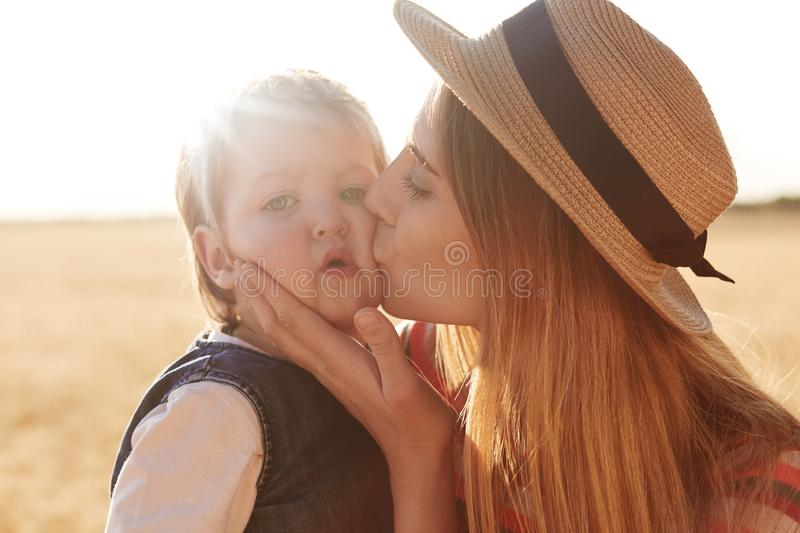 Outdoor picture of loving caring woman with straw hat on head kissing her little daughter, touching her face with hands, posing royalty free stock photo