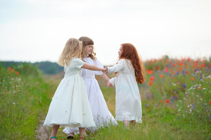 Outdoor play of young girls in summer field. The outdoor play of young girls in summer field stock photo
