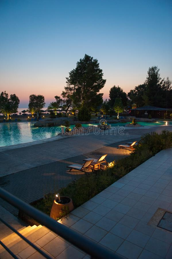 Outdoor pool at sunset, lighting the pool area. rest on the sea, to the pool.  royalty free stock image