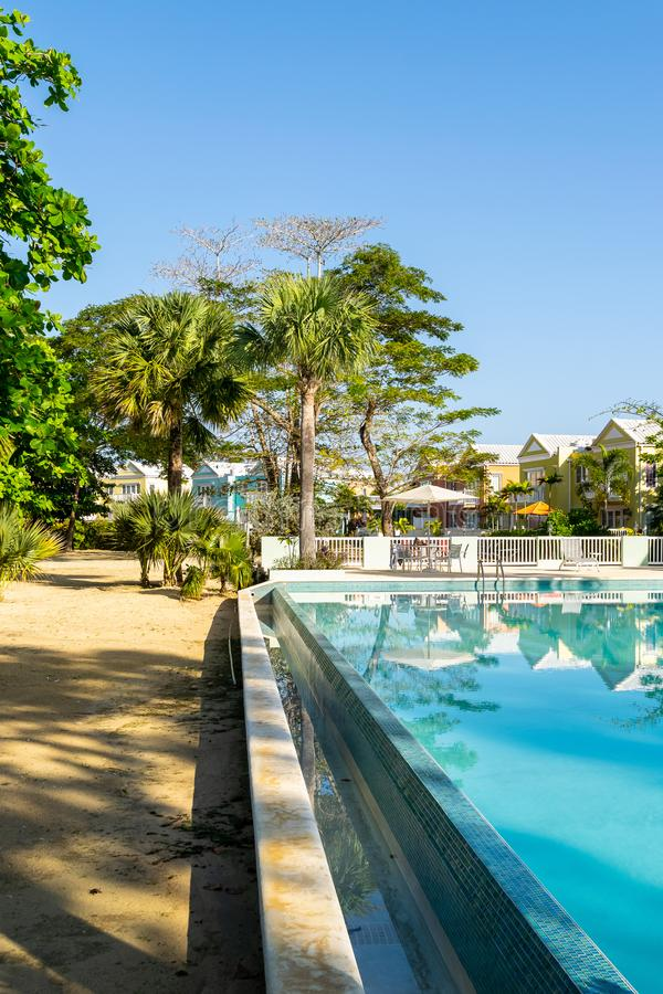 Outdoor pool on white sand beach property of modern residential neighborhood with colorful town houses/homes. stock image