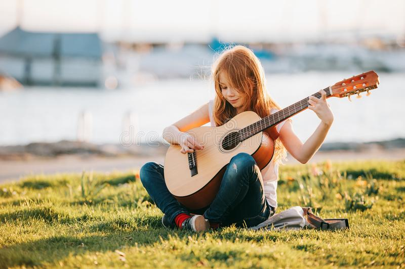 Outdoor portrait of adorable 9 year old kid girl playing guitar outdoors royalty free stock photo