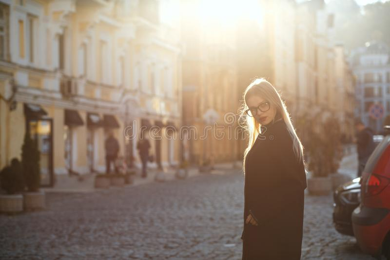 Outdoor portrait of attractive blonde girl wearing glasses and c stock images
