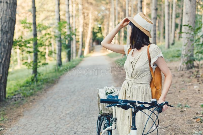 Outdoor portrait of attractive young brunette in a hat on a bicycle. royalty free stock photography